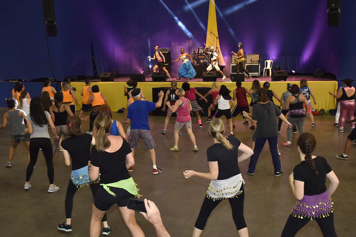 Pessoas praticando dança e zumba no pavilhão, com bailarinos no palco