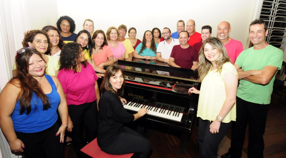 Coralistas do Coral Municipal em foto posada em volta de um piano