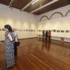 Salão de exposição da Pinacoteca com quadros e visitantes observando e conversando