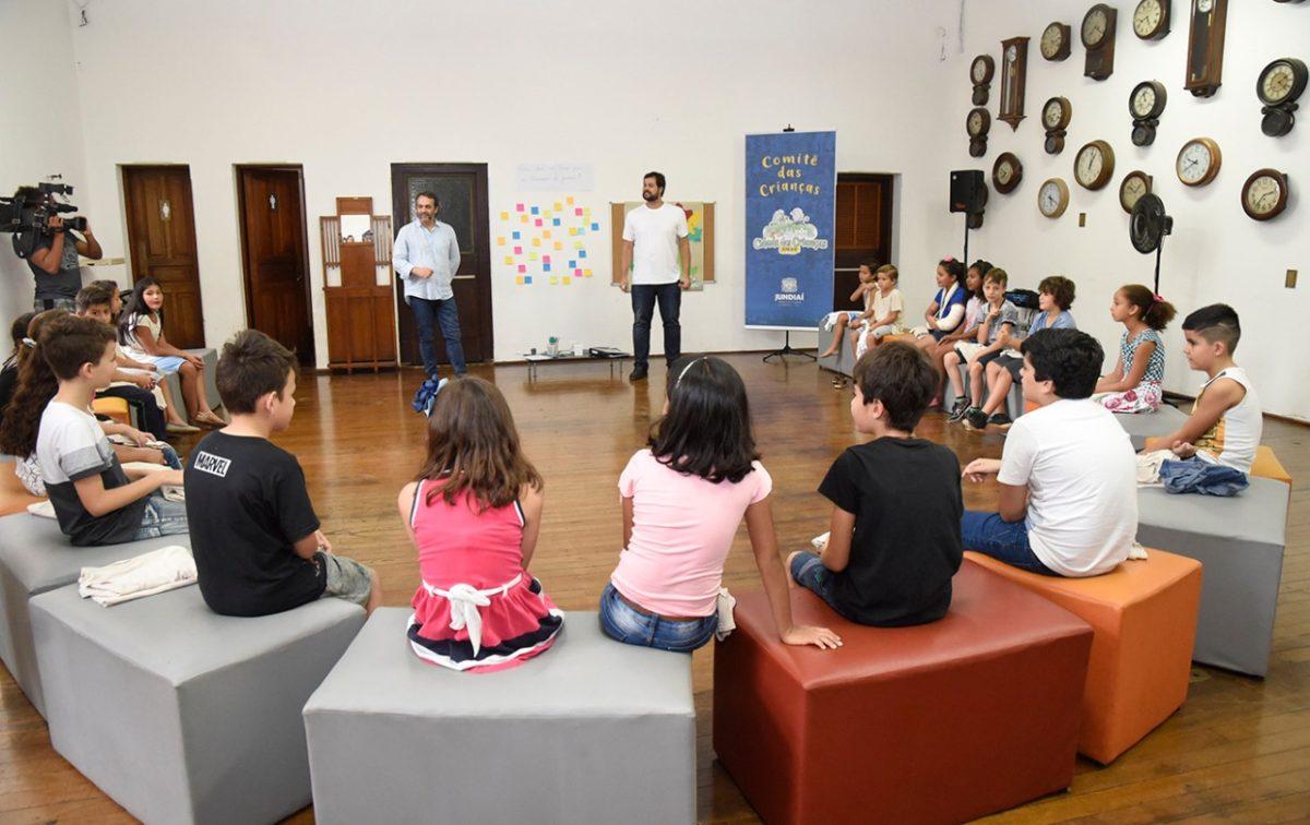 Crianças reunidas em círculo na Sala dos Relógios do Complexo Fepasa, com a mediação do prefeito Luiz Fernando Machado e do gestor de Cultura, Marcelo Peroni