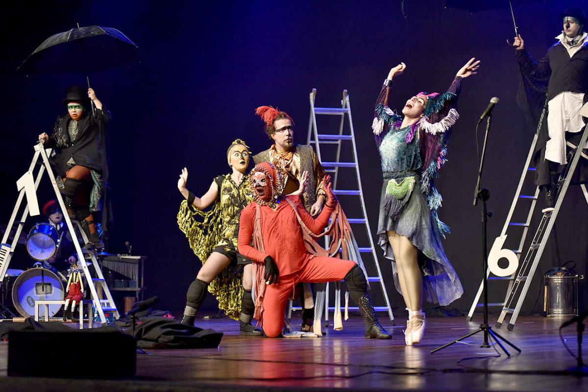 Palco do Polytheama, com atores caracterizados de pássaros, alguns sobre os palcos e alguns em escadas com guarda-chuvas