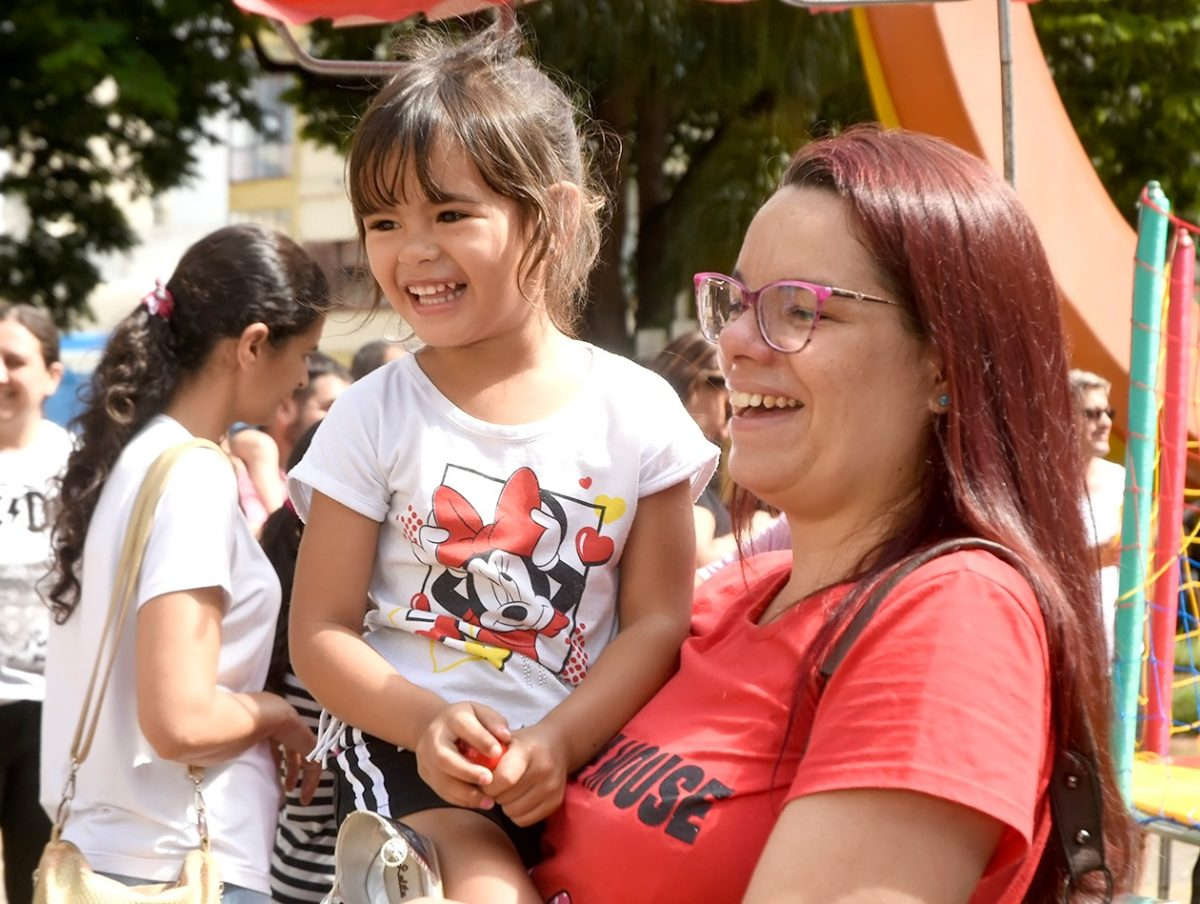 Mãe com criança no colo sorrindo na Praça da Matriz
