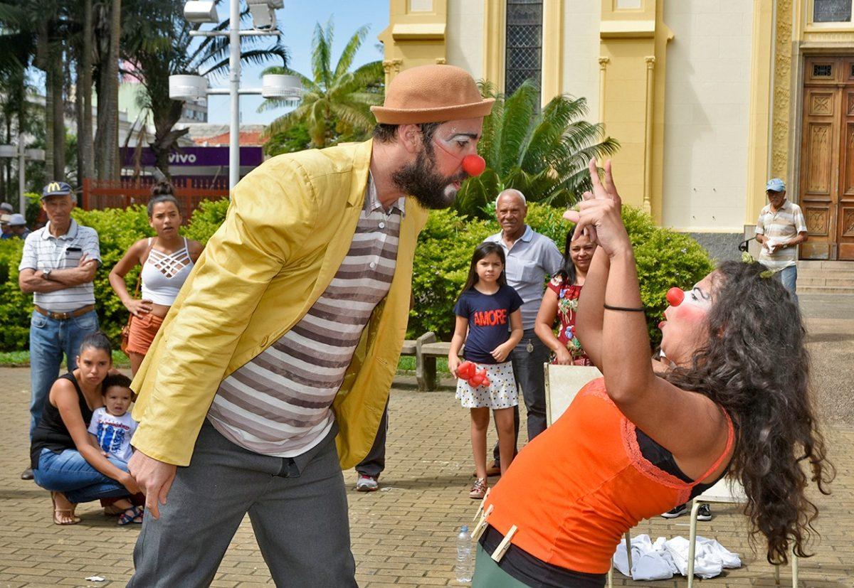Dois atores vestidos de palhaços interagem e o público assiste ao fundo
