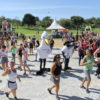 Praça Por do Sol do Parque da cidade, com pessoas fazendo atividade física, junto com os mascotes do parque