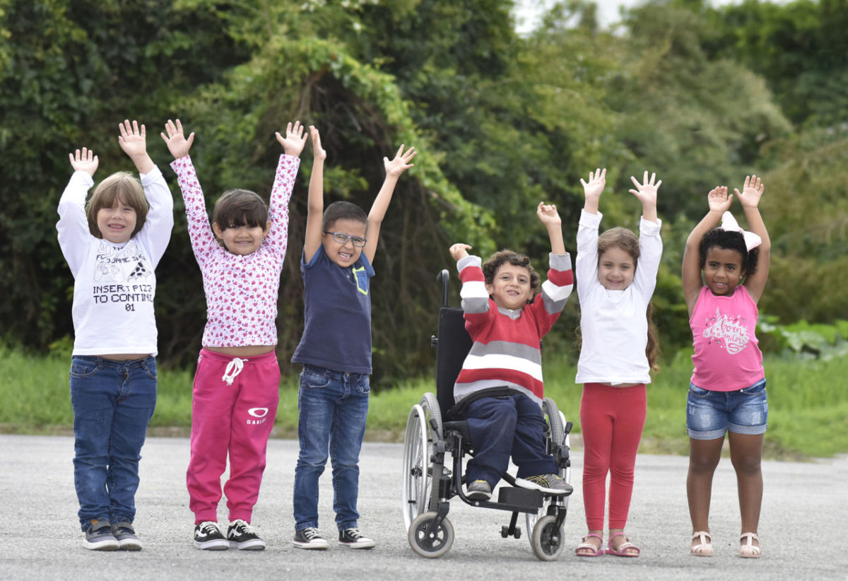 Crianças perfiladas, com as mãos para o alto