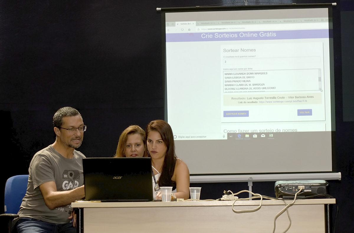 Três pessoas realizando o sorteio online, com transmissão ao vivo pelo Facebook, no palco da Sala Jundiaí do Complexo Fepasa