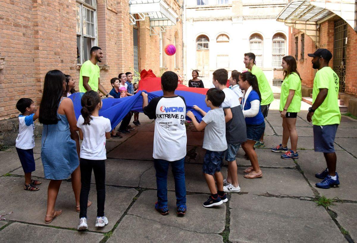 Crianças brincando com lona de pano e bola no pátio do Complexo Fepasa
