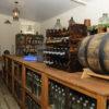 Foto de adega, com garrafas de vinhos, tonéis de madeira e galões de vidro