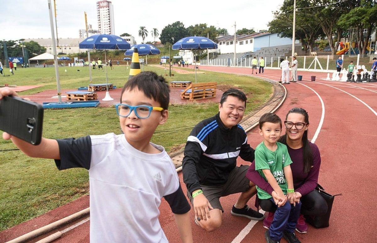 Garoto faz selfie com a família, agachada na pista de corrida do Bolão