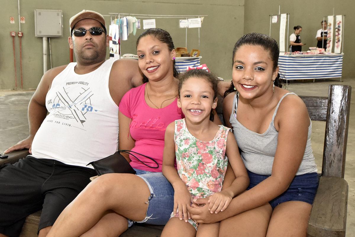 Casal, acompanhado das duas filhas, em foto posada, sentada em um banco de praça, dentro do pavilhão central do parque, com barracas ao fundo