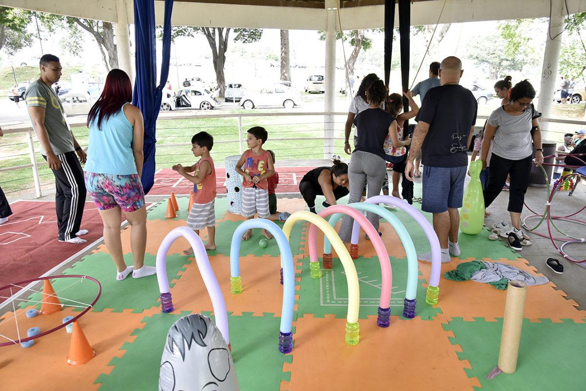 Crianças e adultos, no coreto do parque, com brincadeiras e atividades infantis