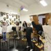 Crianças em semicírculo lançam aviõezinhos coloridos, sobre cadeiras, na Sala dos Relógios do Complexo Fepasa
