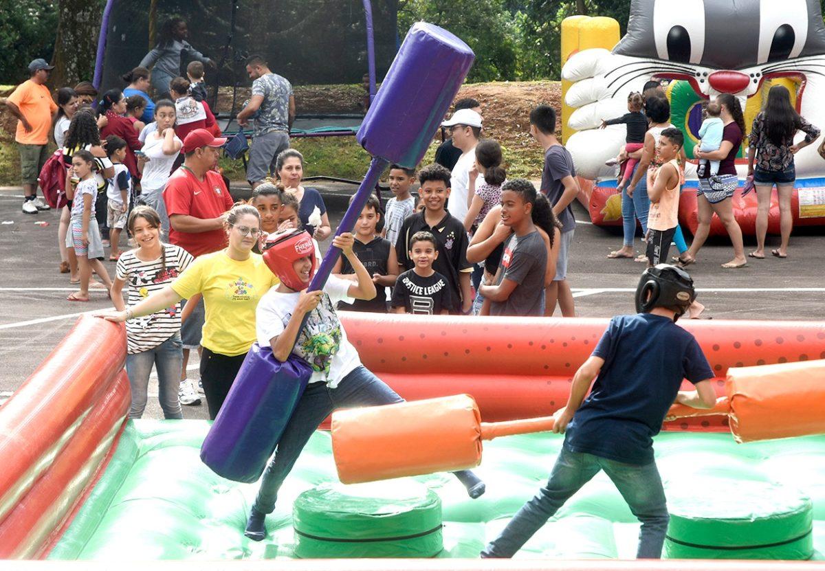 Crianças brincando com luta de bastões em brinquedo inflável