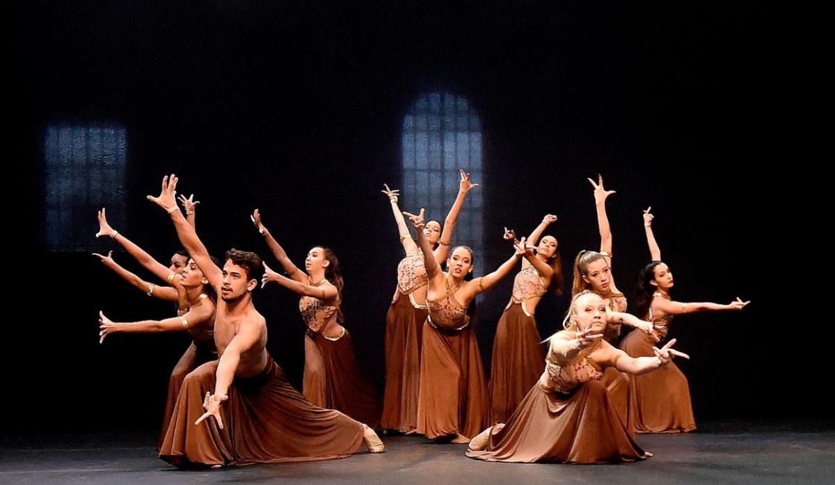 Bailarinas com vestidos longos marrons em apresentação no palco da Sala Jundiaí do Complexo Fepasa, com pano preto no fundo e silhueta de janelas
