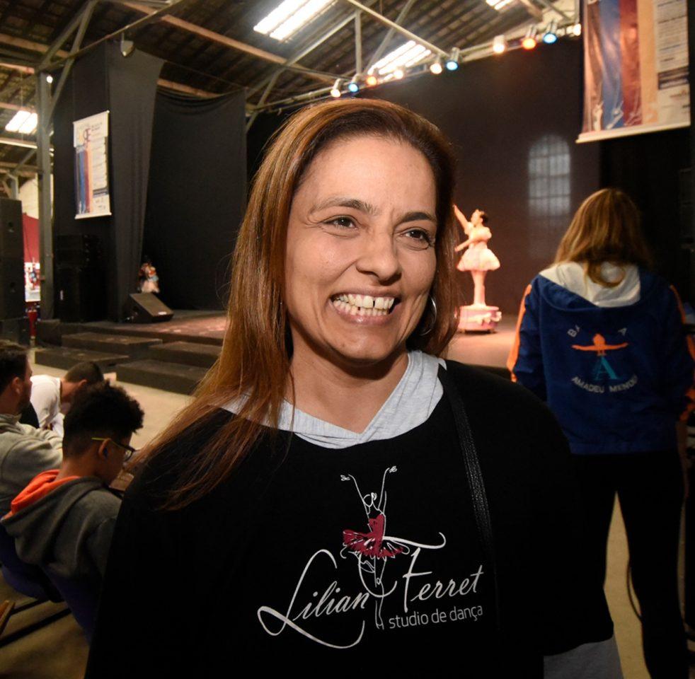 Mulher de cabelos longos sorrindo, com palco ao fundo