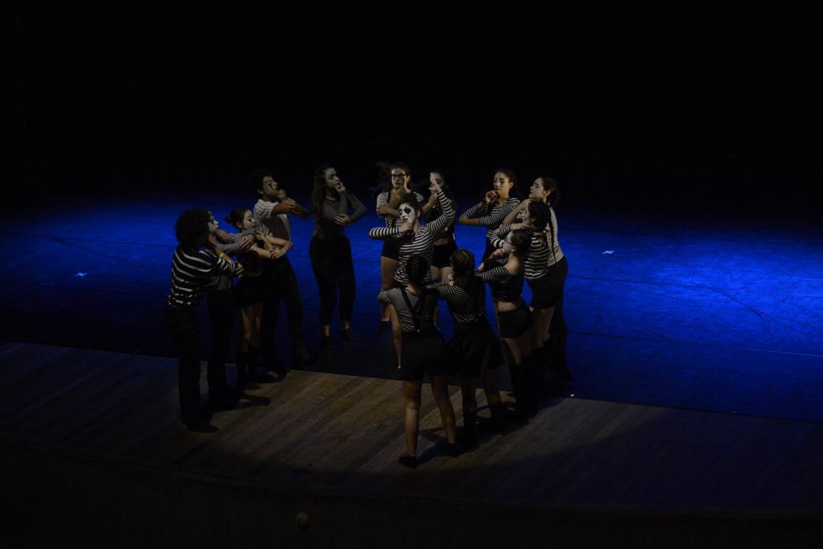 Grupo de dança com 14 bailarinos se apresenta no palco do Polytheama, no escuro, com um foco de luz sobre o grupo, todos com roupa listrada com as cores preta e branca e maquiagem branca na cara