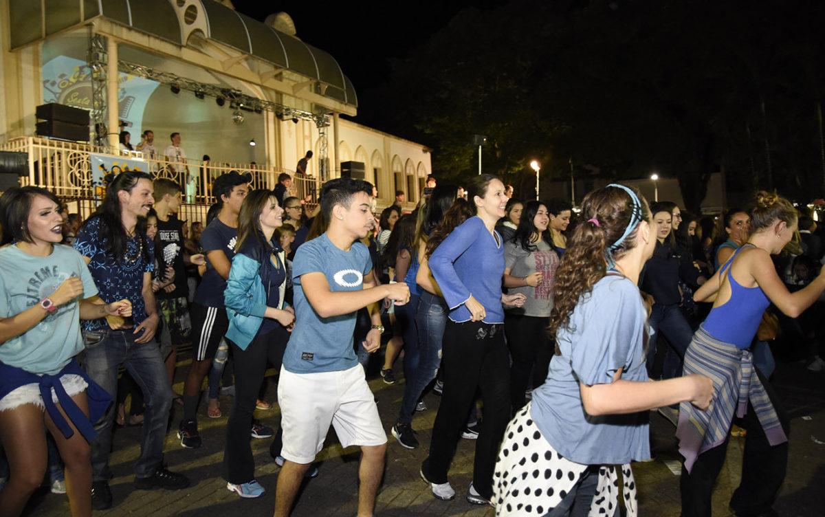 Bailarinos fazem performance de dança em grupo, em frente ao coreto, atrás da igreja Matriz