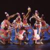 Nove bailarinas infantojuvenis vestidas com fantasias de cupcakes em coreografia circular no palco