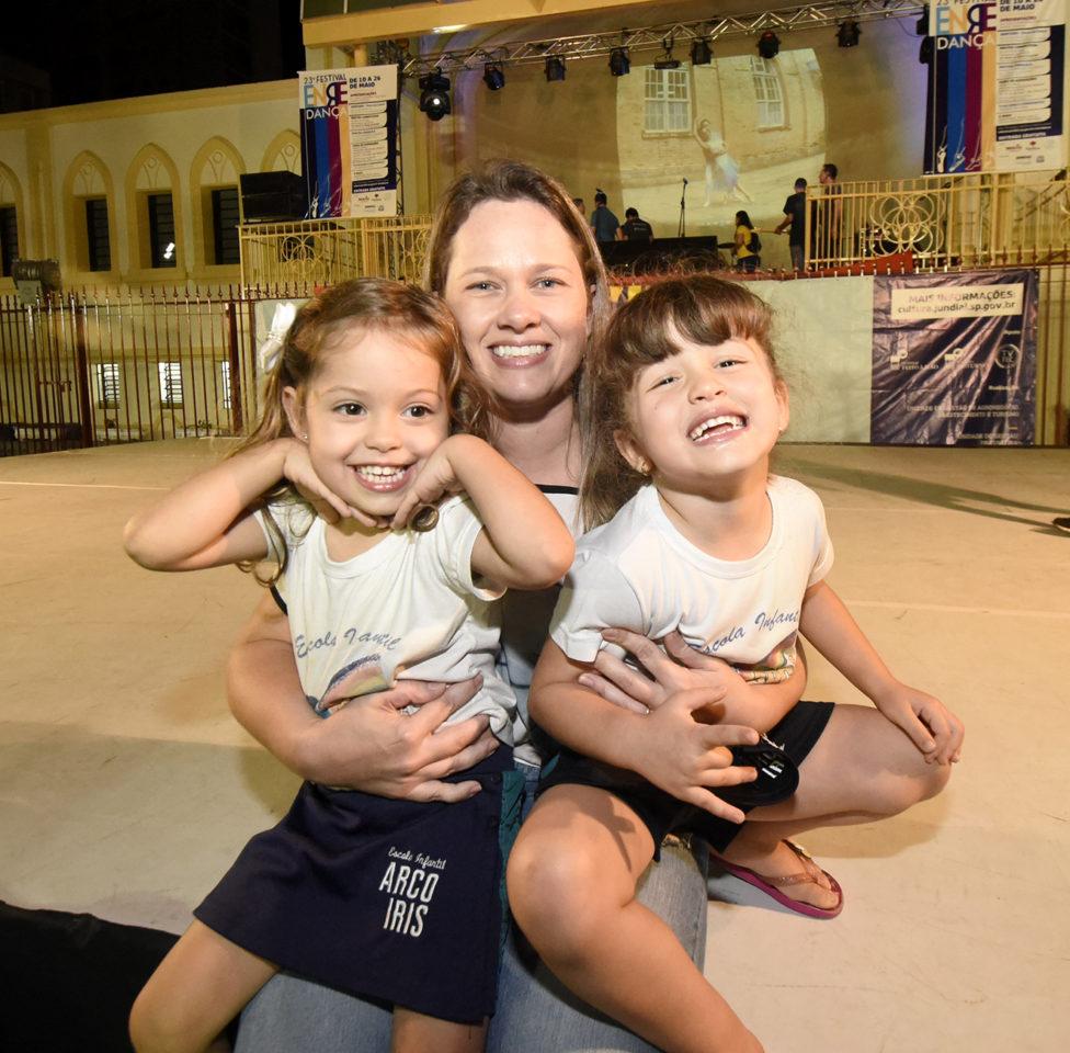Mulher sentada no palco de dança montado na praça carrega no colo as duas filhas gêmeas, de cerca de quatro anos,