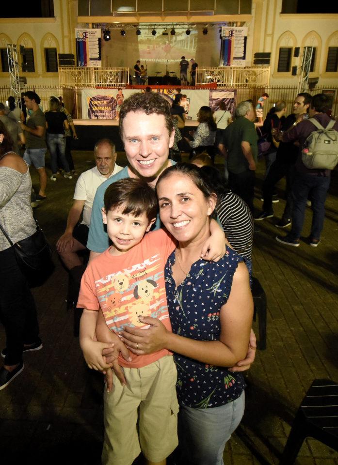 Casal e filho em foto posada, em pé, com os palcos montado e do Coreto e fundo da Matriz atrás, cercados de pessoas