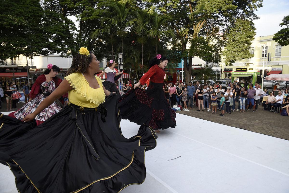 Bailarinas em apresentação de dança flamenca, em palco montado na praça, com público ao fundo