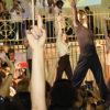 Bailarinos fazem performance de dança em grupo, com as mãos para o alto, m frente ao coreto, atrás da igreja Matriz