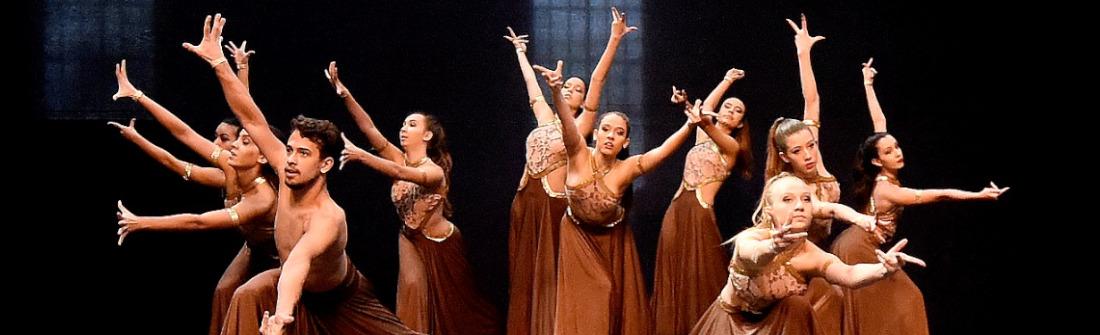 Bailarinas com vestidos longos marrons em apresentação no palco da Sala Jundiaí do Complexo Fepasa, com pano preto no fundo e silhueta de janela