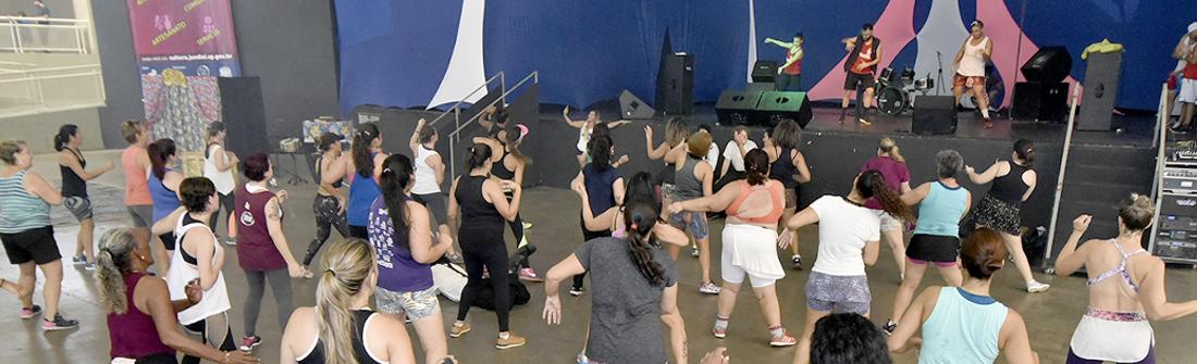 Mulheres praticando zumba, com instrutores sobre o palco do pavilhão do parque