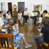 Crianças sentadas em cadeiras em círculo, na Sala dos Relógios do Complexo Fepasa
