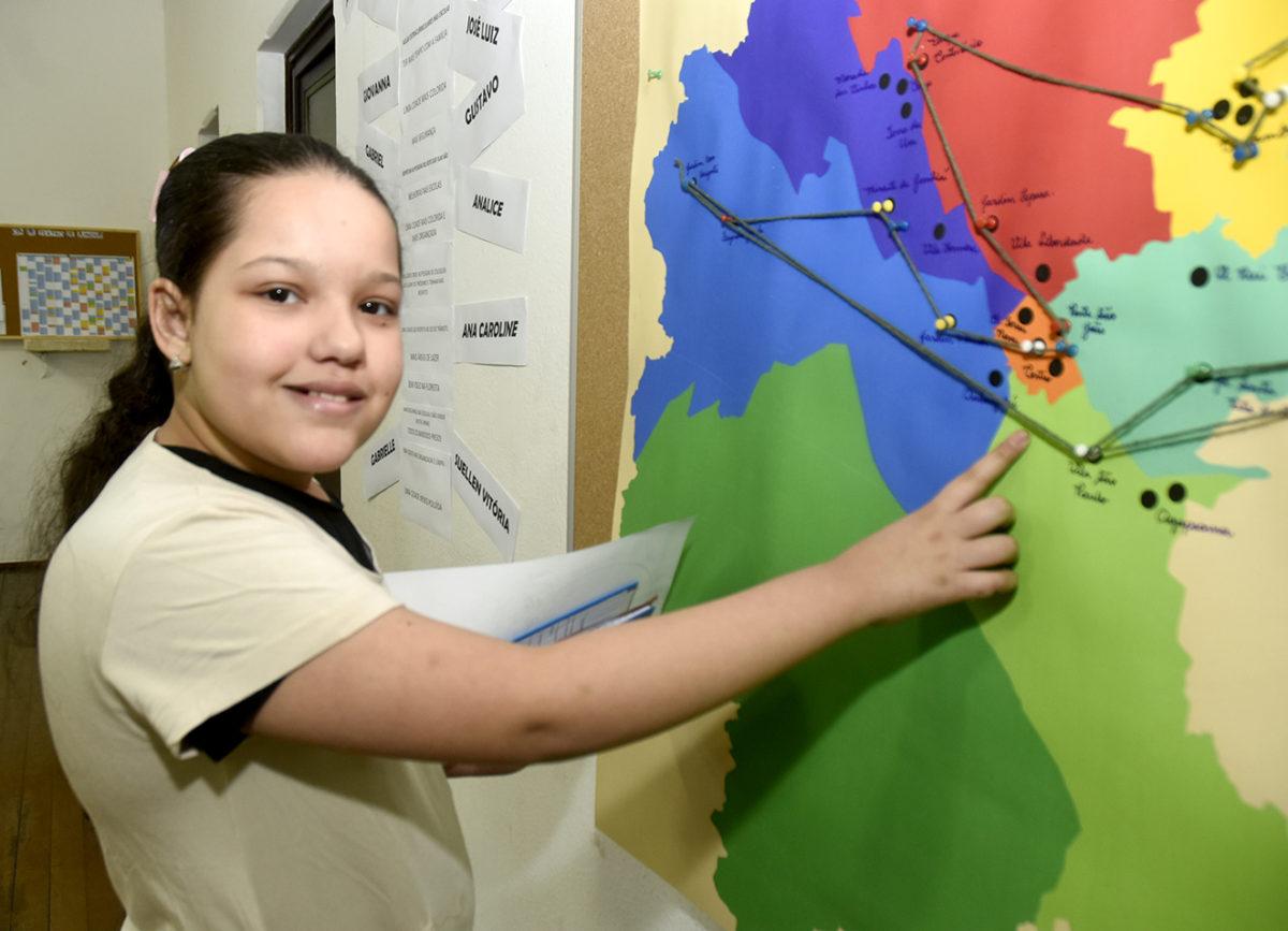 Foto posada de menina que aponta para mapa de Jundiaí afixado na parede com cores diferentes para cada região