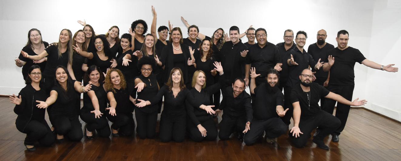 Foto posada de coralistas, usando roupa preta e fazendo gestos espontâneos com os braços