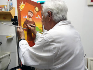 Homem em frente a uma tela, com pincel na mão e jaleco