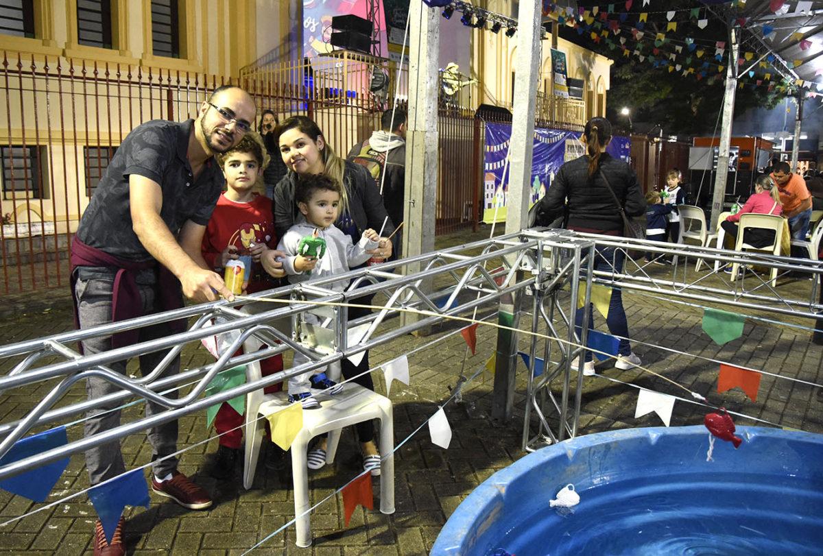 Casal com os filhos, apoiados em divisória de metal, brincam de pesca sobre caixa d'água