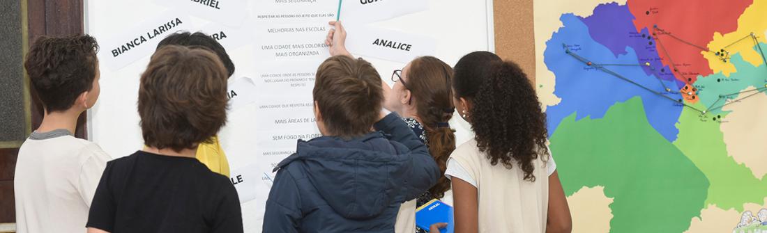 Crianças olham e apontam em direção a um painel com nomes, com detalhe para as suas cabeças, e mapa de Jundiaí colorido à direita