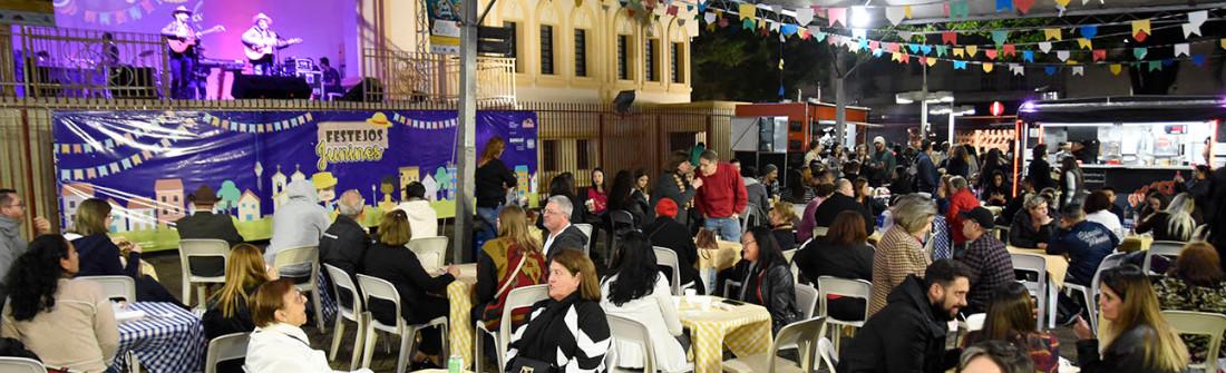 Praça do Coreto, com público expressivo, em foto noturna e com decoração junina