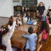 Mesa de madeira, com crianças sentadas ao redor, algumas com as mãos levantadas, enquanto atendem a instruções de homem em pé na cabeceira da mesa