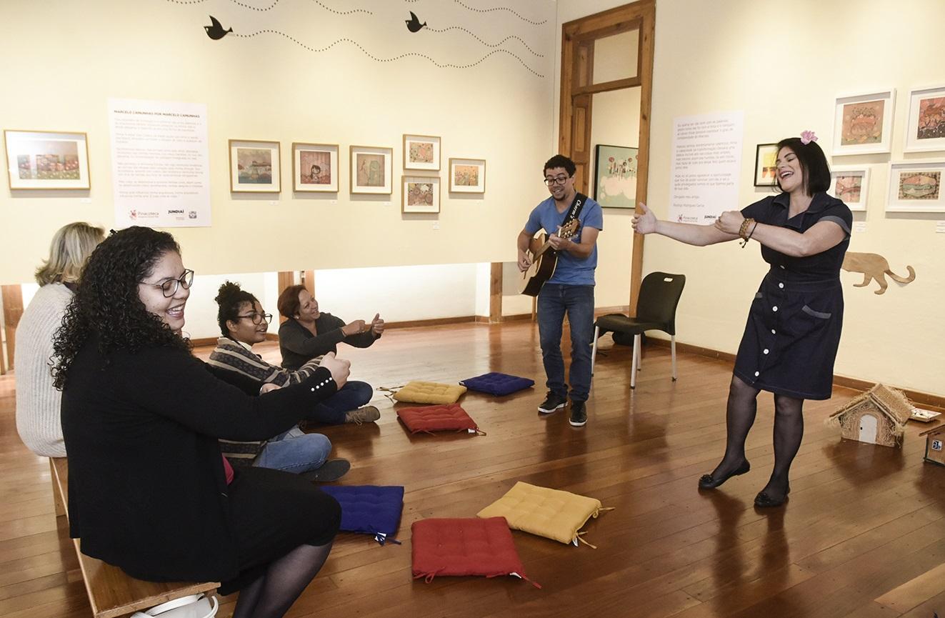 Sala da Pinacoteca, com quadros expostos, e um casal apresentando com violão para mães e crianças sentadas sobre almofadas no chão