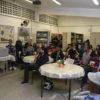 Sala de aula, com mesas espalhadas, e pessoas sentadas em cadeiras, assistindo a uma apresentação