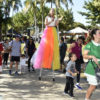 Adultos e crianças acompanham intervenção artística, com mulher andando de perna de pau