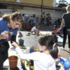 Espaço com diversas crianças e adultos, com material de pintura espalhado pelo chão, e mulher dando as instruções para a atividade
