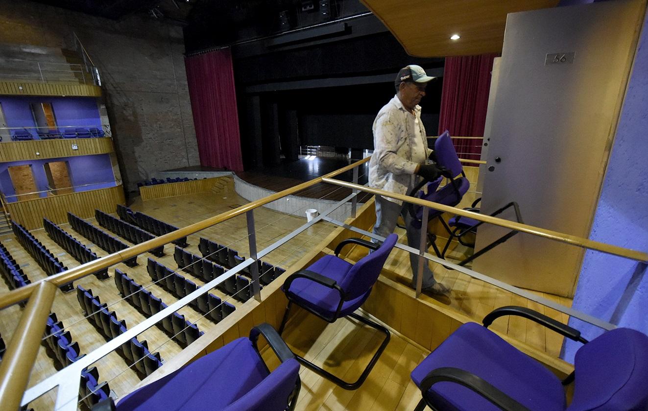 Homem carrega cadeira de dentro de camarote do teatro, com plateia e palco ao fundo