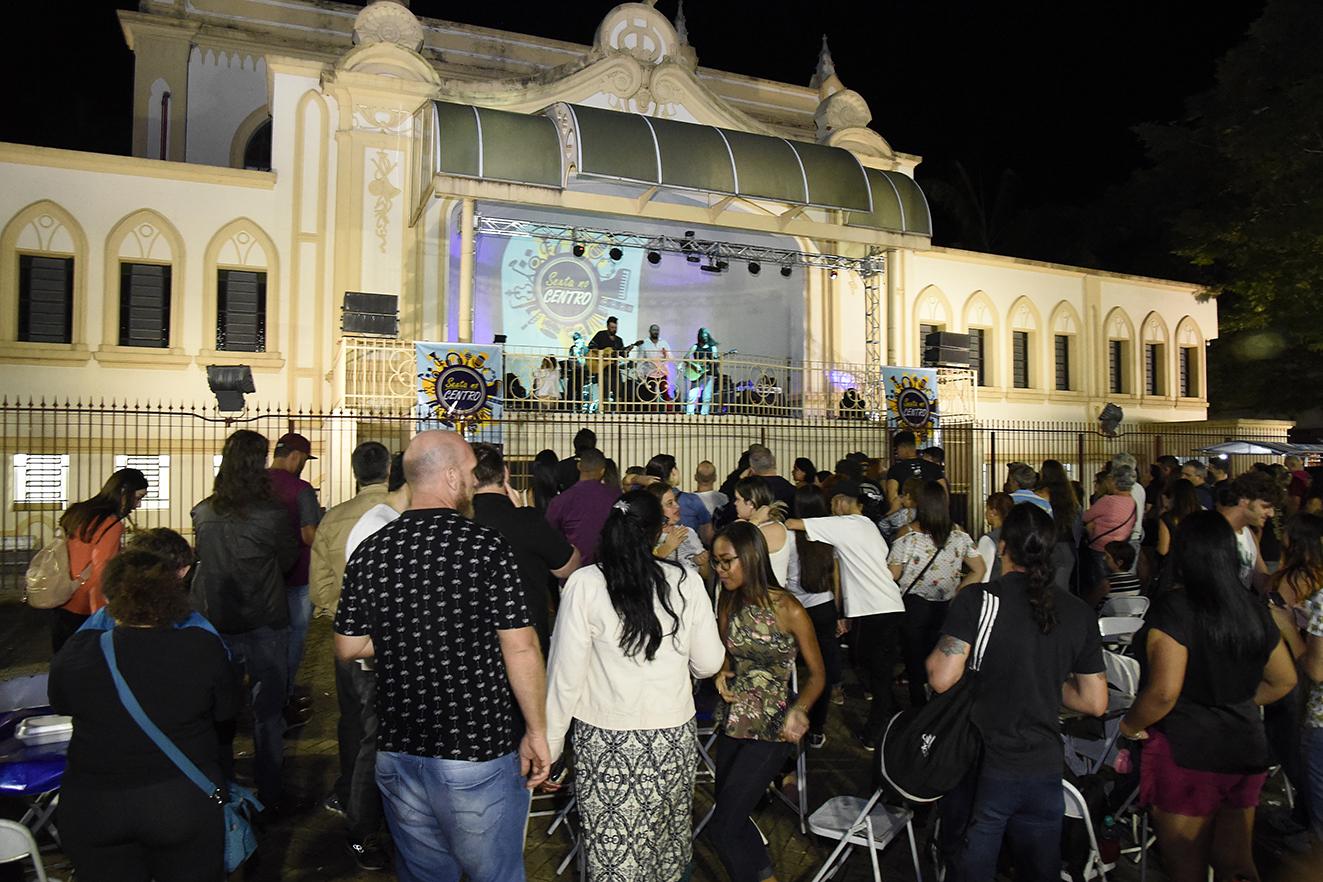 Foto noturna do palco do Coreto iluminado, com apresentação de banda e público assistindo sentado e em pé