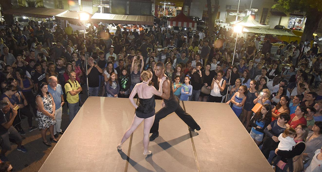 Foto noturna com enquadramento de cima, com apresentação de dupla em palco e público expressivo em volta