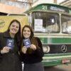 Duas mulheres seguram passaporte, em frente a ônibus estacionado