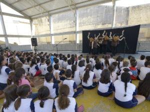 Crianças sentadas sobre o chão de uma quadra, assistindo a apresentação de atores sobre um tablado
