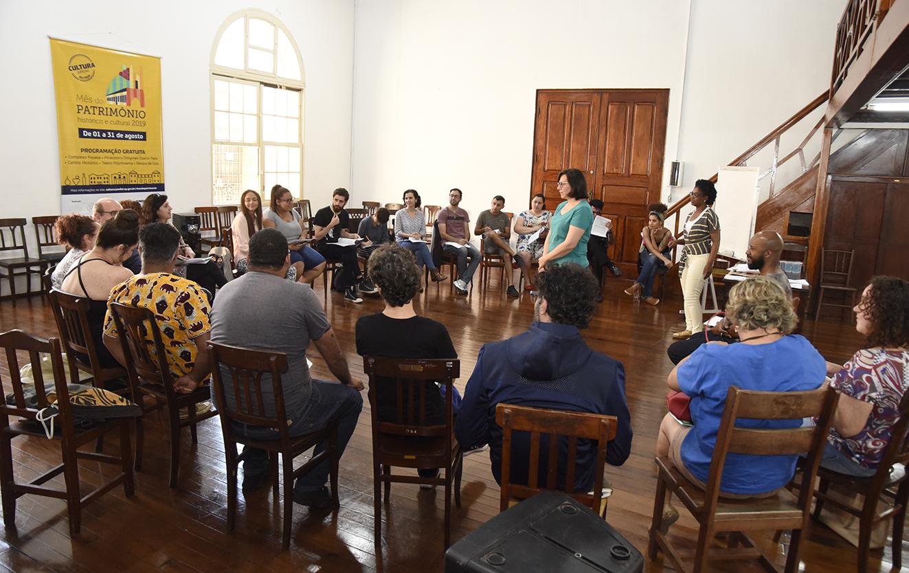 Pessoas sentadas em círculo, em situação de reunião, com mulher em pé no centro mediando a conversa