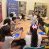 Crianças e um adulto sentados ao redor de uma mesa, conversando e interagindo