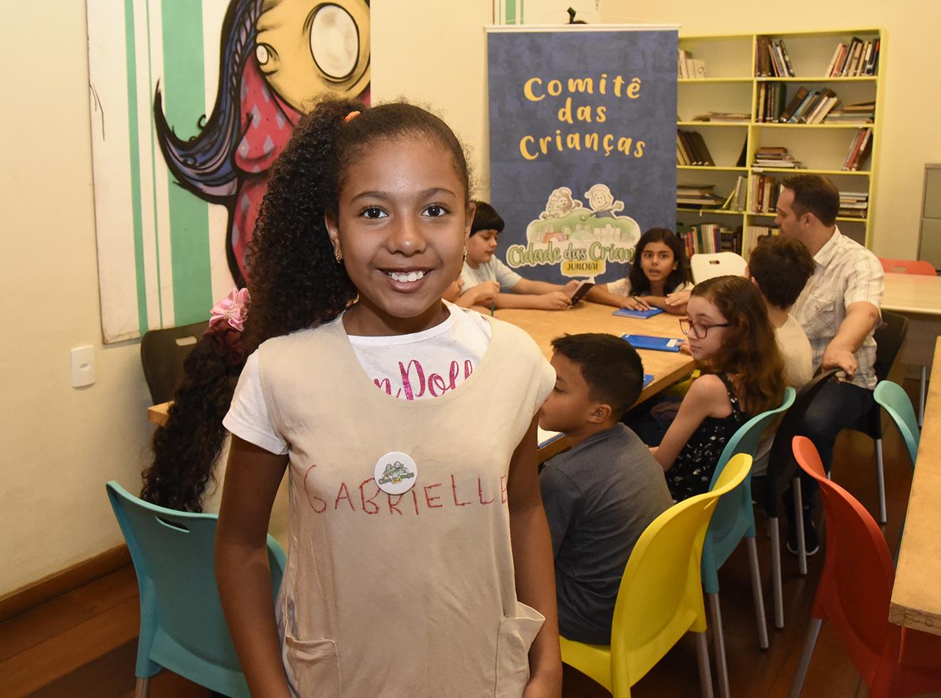 Foto posada de menina sorrindo, com o cabelo preso para o lado, e crianças sentadas ao redor de uma mesa ao fundo