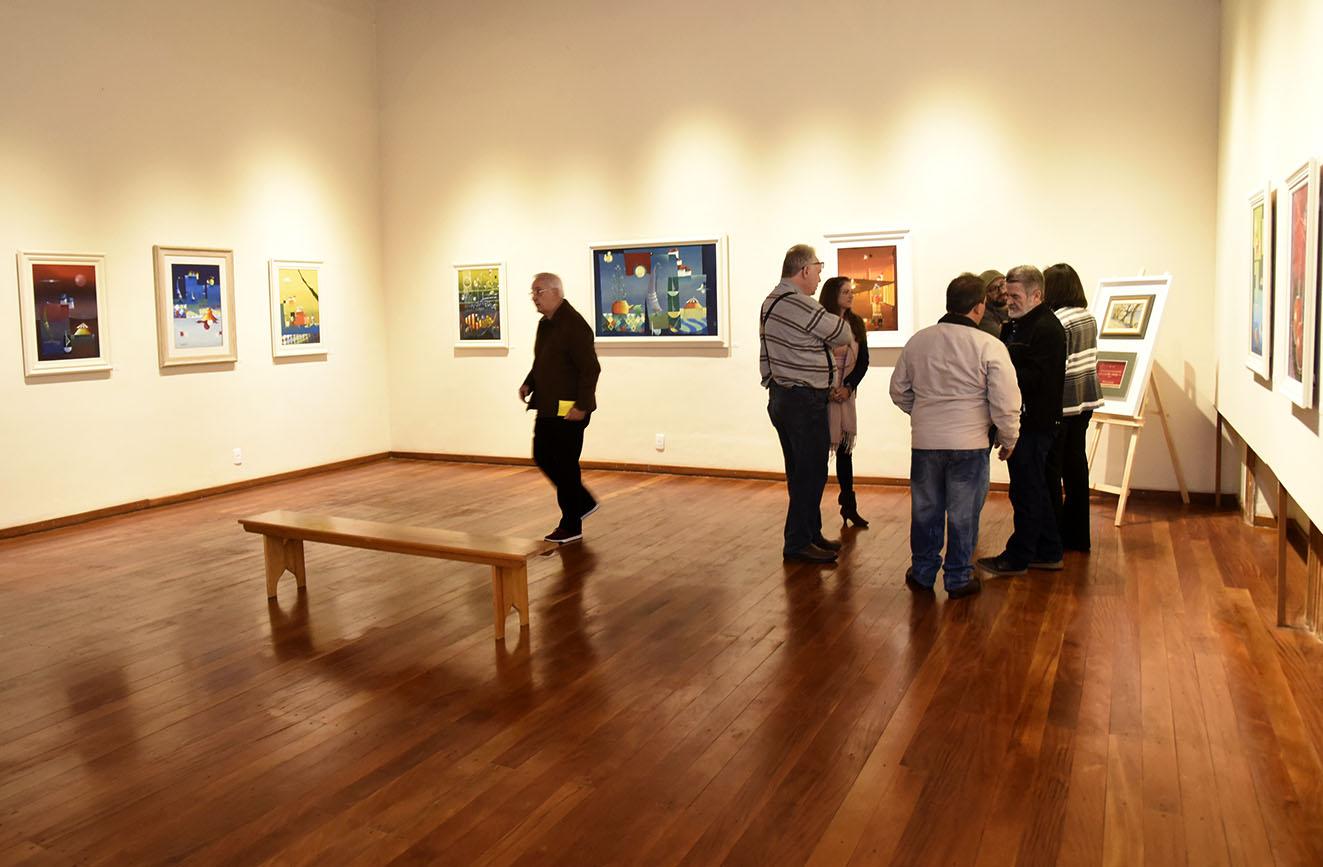 Sala de exposições, com quadros na parede, e pessoas transitando pela sala