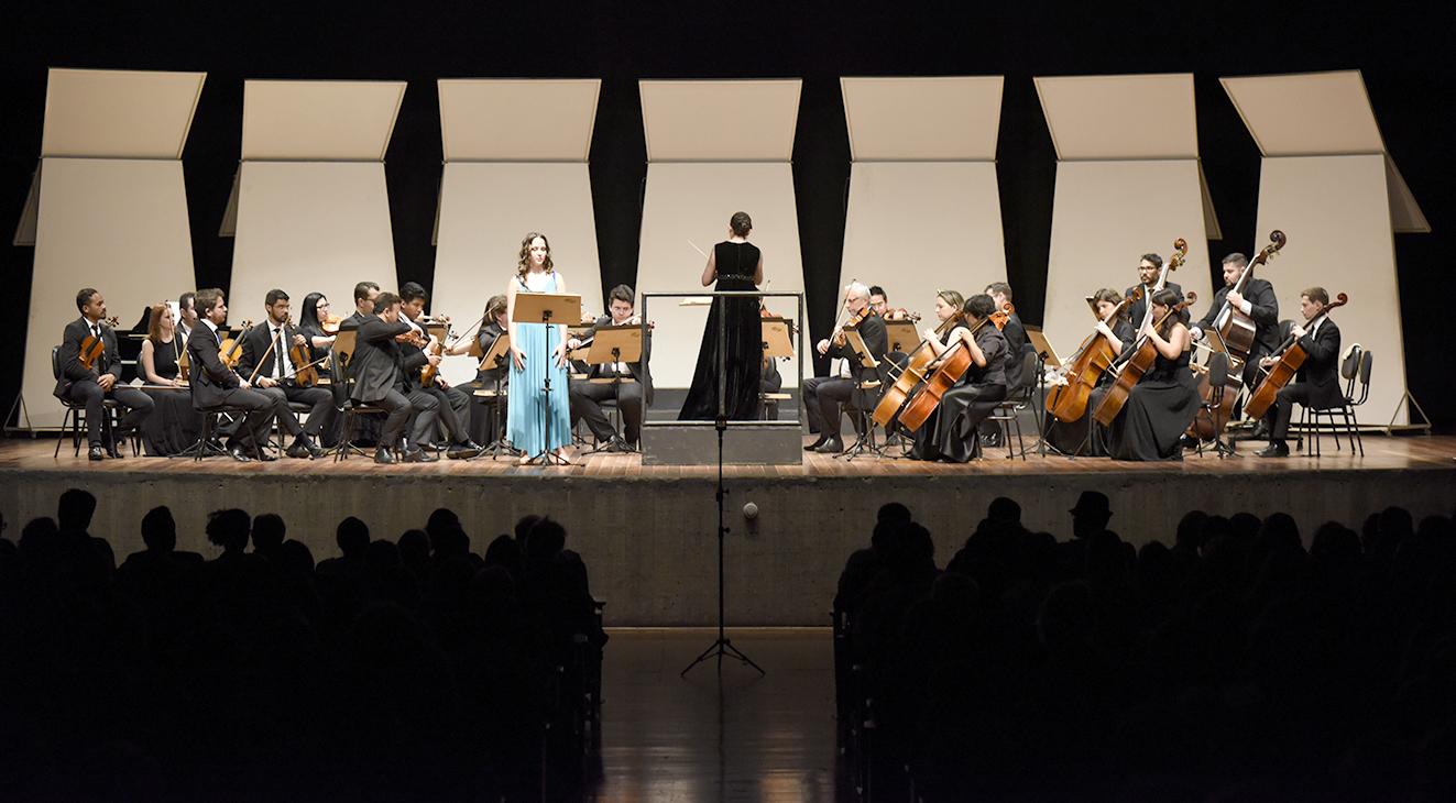 Palco de teatro iluminado, com músicos em performance, e duas mulheres em pé, uma regendo e a outra cantando, e silhueta de público na penumbra